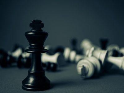 czarny pionek szachowy na tle innych pionkow
